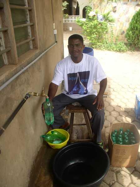 Claude unser Techniker in KPalimé füllt sauberes Trinkwasser in PET-Flaschen